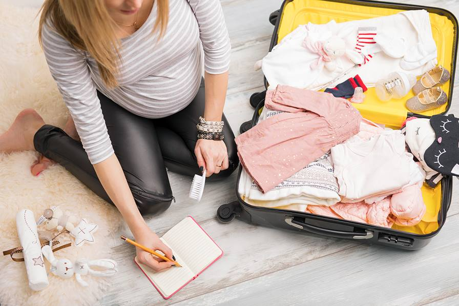 A mom packing baby items in a suit case